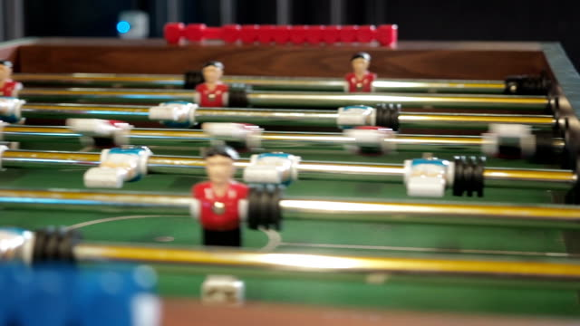 Active people playing foosball. table soccer plaers. Friends play together table football