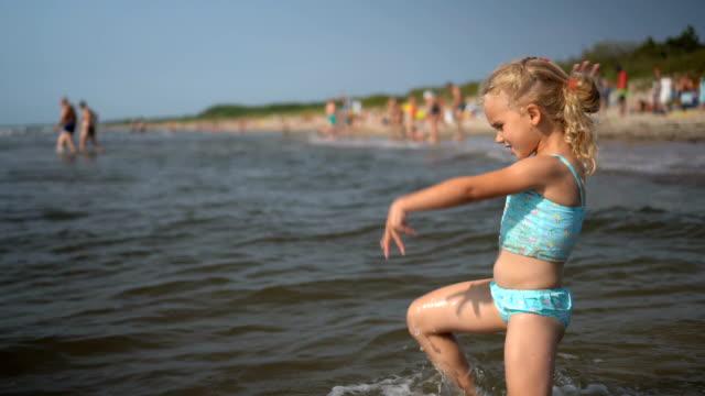 aktiv lekfull liten flicka dans vada genom havsvattenvågor. roligt barn - förskoleelev bildbanksvideor och videomaterial från bakom kulisserna