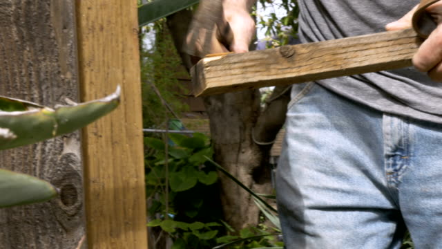 Active retired senior man reusing an old piece of wood to fix fence