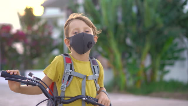 Active school kid boy in medical mask riding a bike with backpack on sunny day. Happy child biking on way to school. You need to go to school in a mask because of the coronavirus epidemic
