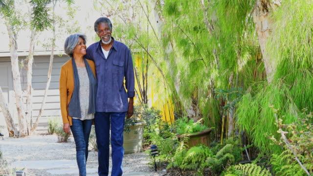 aktiv senior african american par promenader genom trädgården hemma - senior walking bildbanksvideor och videomaterial från bakom kulisserna