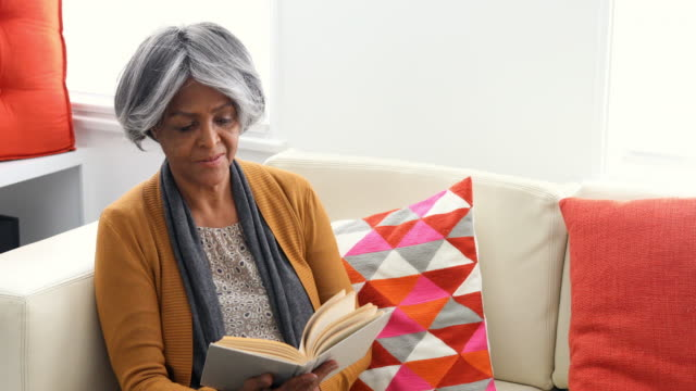 Active Senior African American Woman Reading on the Sofa video