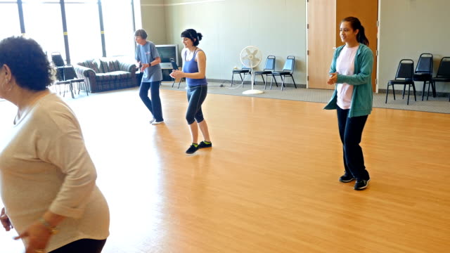 Active senior and young women learning to line dance video