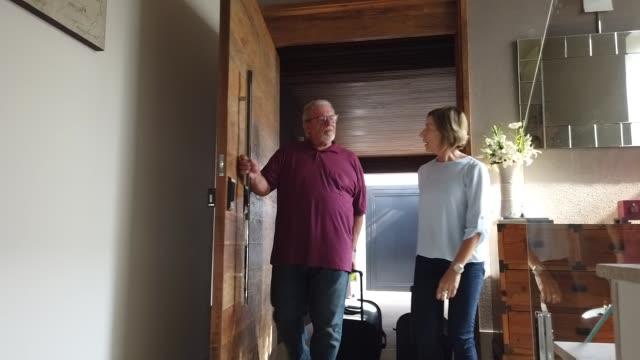 aktiva senior par som anländer från resan - ytterdörr bildbanksvideor och videomaterial från bakom kulisserna