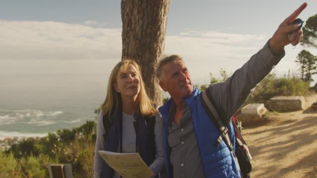 Aktives Seniorenpaar auf der Karte im Wald – Video