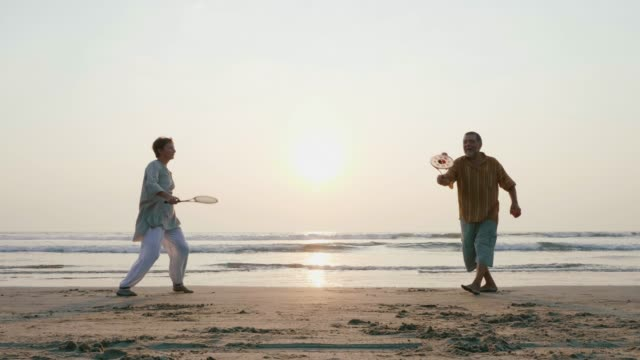 active senior couple playing tai chi ballon ball at the beach in slow motion. - badminton stock videos & royalty-free footage