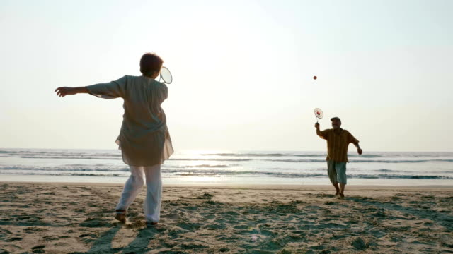 Active senior couple playing tai chi ballon ball at the beach. video