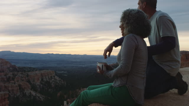 4k uhd: active senior couple soaking in bryce canyon sunrise - parco nazionale video stock e b–roll
