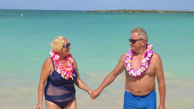 Active Senior Couple Walking On The Ocean in Hawaii in 4K slow motion 60fps