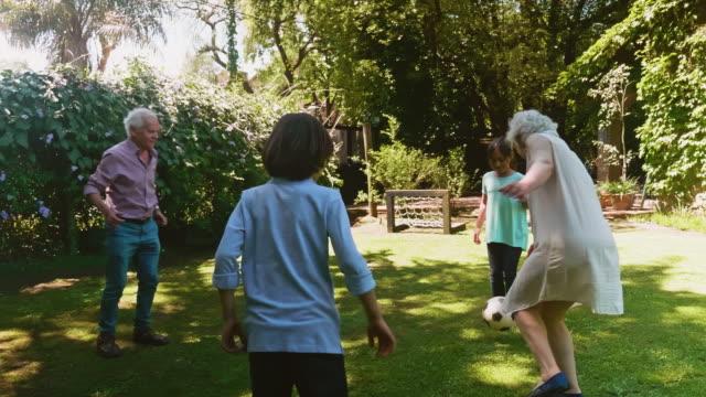 Active Senior Footballers Kicking Ball with Grandchildren