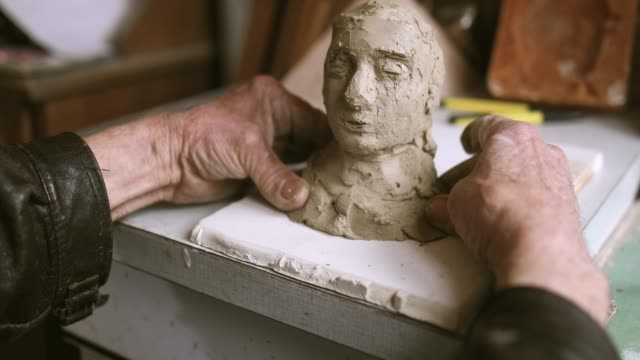 Active senior making statue of clay
