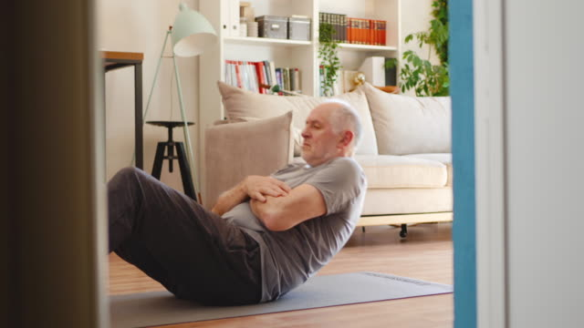 Active senior man doing sit-ups at home Active senior man doing sit-ups at home baby boomers stock videos & royalty-free footage