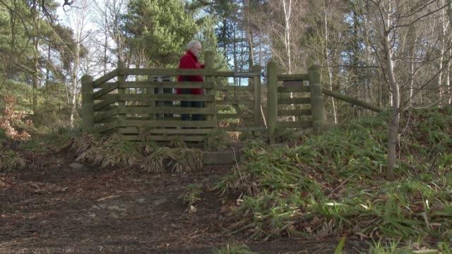 Active senior man going through a gate onto a foot path