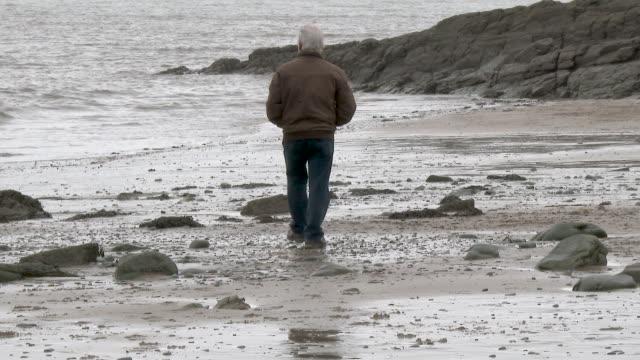 active senior man on beach - samotność filmów i materiałów b-roll