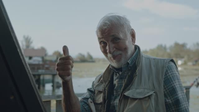 vídeos de stock e filmes b-roll de active senior man showing thumbs up - margem do lago
