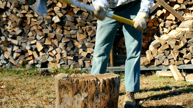 etkin komuta sizde bir balta bir ağaç kütüğü sallanır. - şömine odunu stok videoları ve detay görüntü çekimi