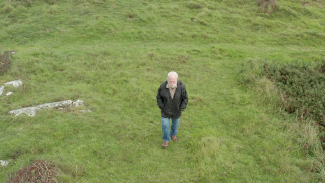 Active senior man walking along a coastal path in Dumfries and Galloway 4K drone footage tracking a senior man as he walks along a coastal path in south west Scotland galloway scotland stock videos & royalty-free footage