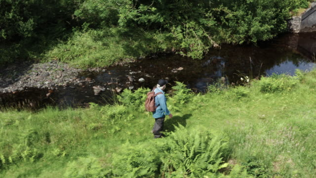 Active senior man walking beside a small slow flowing river in a remote rural south west Scotland video