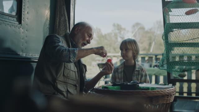 aktive senioren lehren enkel, wie man angeln köder - angelhaken stock-videos und b-roll-filmmaterial