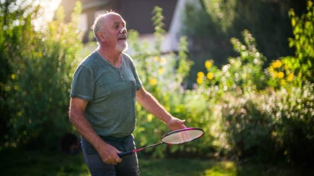 活動的なシニアは、日当たりの庭でバドミントンを再生します - スポーツ バドミントン点の映像素材/bロール