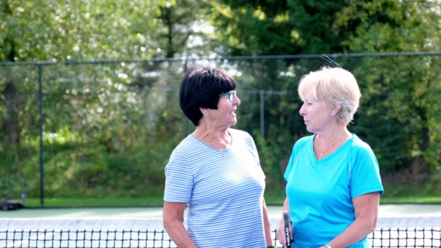 Active senior woman enjoying their retirement Two active senior woman on a tennis court playing Pickleball. They are enjoying their retirement years. Active senior woman short hair stock videos & royalty-free footage