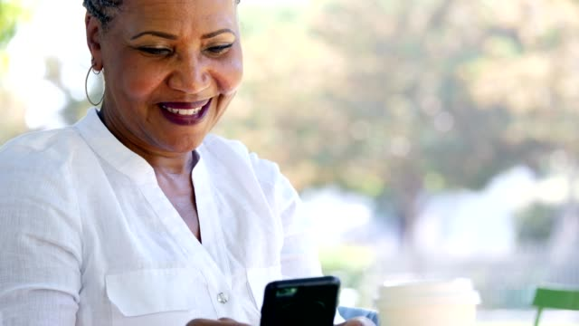 Active senior woman laughs while texting with her family