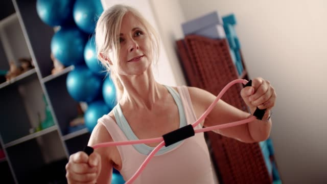 Active senior woman stretching her arms with resistance band video