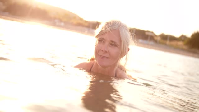 active senior woman swimming in the sea at sunset - gente serena video stock e b–roll