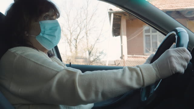 active senior woman taking her car to go to work. driving with a protective mask and protective gloves. illness prevention. - essential workers stock videos & royalty-free footage