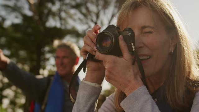 Aktive Seniorin beim Fotografieren im Wald – Video