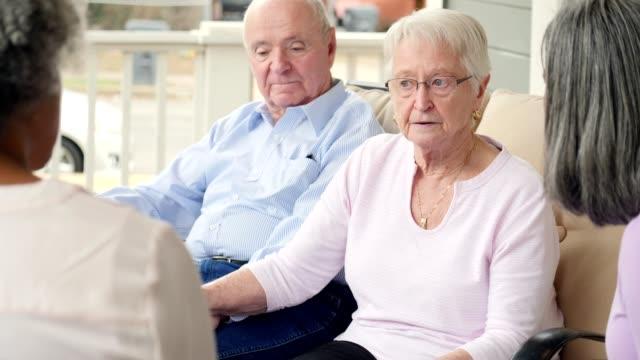 aktive ältere frau spricht mit einer gruppe von freunden im ruhestandsgemeinschaft - storytelling videos stock-videos und b-roll-filmmaterial