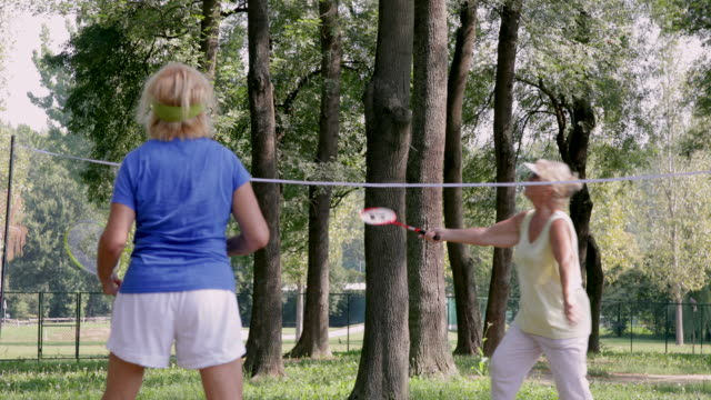 Active seniors playing badminton in the shade video