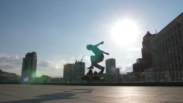 外でキックフリップトリックをするアクティブなスケートボーダー - スケートボード点の映像素材/bロール