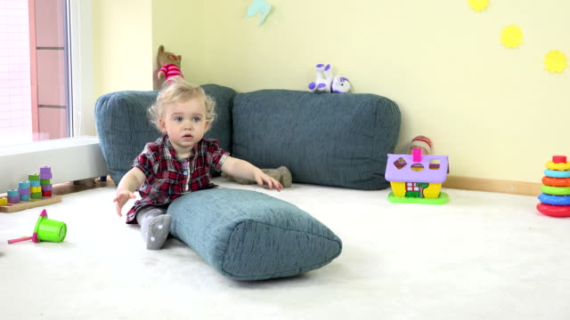 Active toddler girl climb on blue huge pillow and show true emotions at camera. video