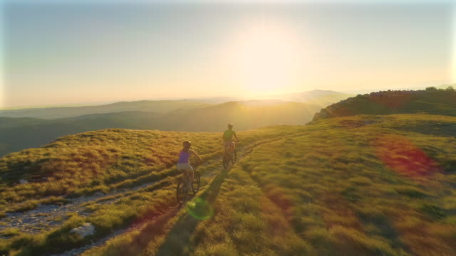 aerial: active tourist couple speeding down the grassy hill on their bicycles. - andare in mountain bike video stock e b–roll