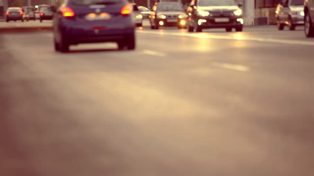 Active traffic on road at evening time, cars passing with lights on