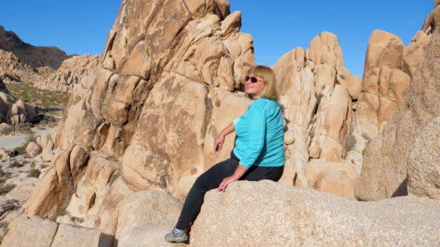 Active Woman Sits High On The Edge Of The Rock, Rejoicing The View And Smiling video