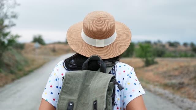 sırt çantası olan aktif bir kadın otoyol arka görünümünde gidiyor. 4k red kamerada orta yakın çekim - i̇nsan sırtı stok videoları ve detay görüntü çekimi
