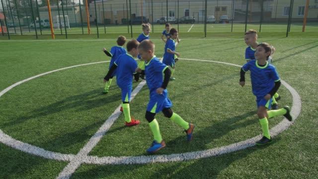 ウォームアップ中にプレーするアクティブな若いサッカー選手 - サッカークラブ点の映像素材/bロール