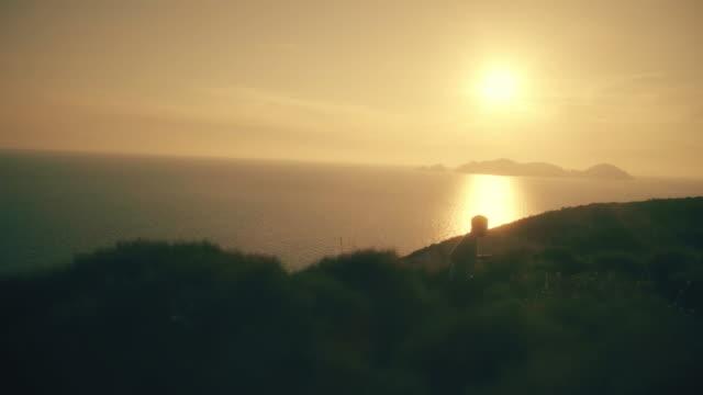 aktiva unga mannen kör längs ett spår på en kulle med landskapet i havet vid solnedgången på ponza ön slowmotion drone dolly - jogging hill bildbanksvideor och videomaterial från bakom kulisserna