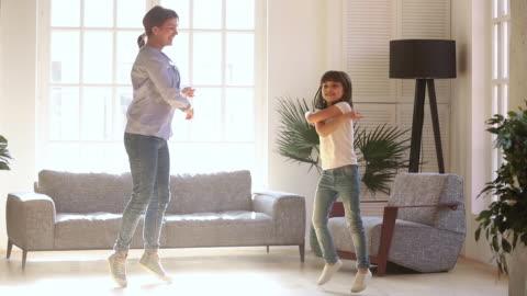 vídeos y material grabado en eventos de stock de joven madre activa y niña hija bailando en la sala de estar - bailar