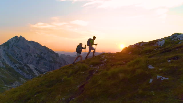 AERIAL: Active young tourists hiking up a grassy mountain in the Alps at sunset.