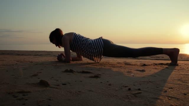aktiv ung kvinna streching och öva yoga på stranden vid solnedgången. - korslagda ben bildbanksvideor och videomaterial från bakom kulisserna