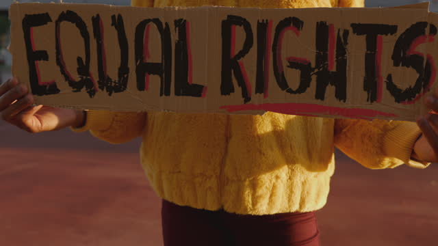 Activist for equal rights Young woman holding a message written on a cardboard civil rights stock videos & royalty-free footage