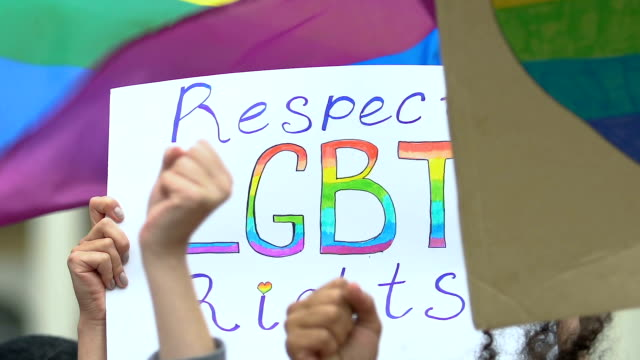 Activists chanting with raised hands waving banners for LGBT rights, pride march Activists chanting with raised hands waving banners for LGBT rights, pride march lgbtqi rights stock videos & royalty-free footage