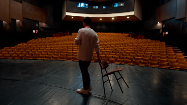 Actor drag a chair on a theater stage There is one young man, age 23. He is in theater and he have a rehearsal. He is an actor,he read and learn his text. actor stock videos & royalty-free footage