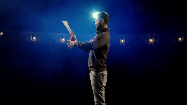 Actor performing a monologue in a theater Medium shot of an actor performing a monologue in a theater while holding his script actor stock videos & royalty-free footage