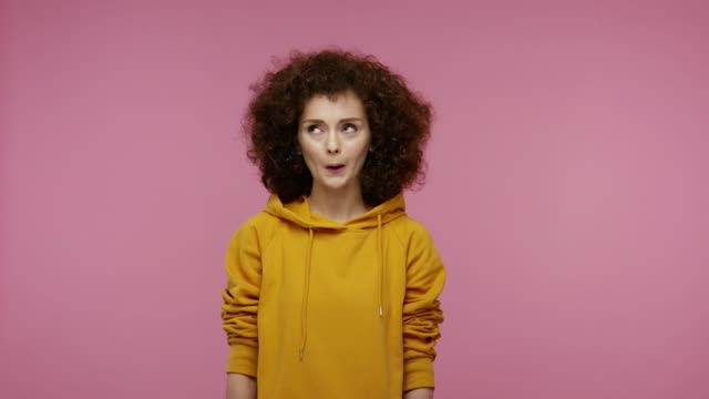 Actress girl afro hairstyle in hoodie laughing and showing different facial emotions, amazement, puffing cheeks