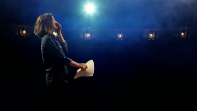 Actress rehearsing in a theater Medium close-up of an actress rehearsing a monologue in a theater while holding her script actor stock videos & royalty-free footage
