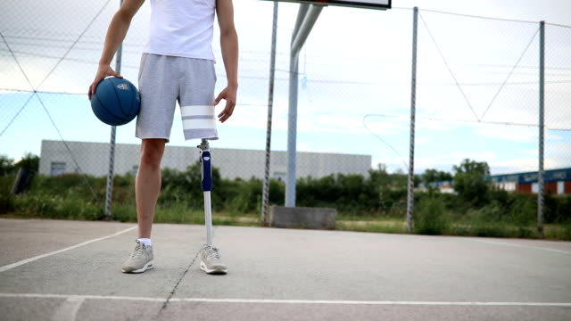 Adaptive athlete on a basketball court Young amputee with a artificial leg, enjoying his time outdoors by playing basketball. conquering adversity stock videos & royalty-free footage